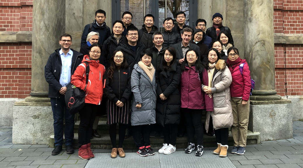 Besucherinnen und Besucher aus Shanghai stehen vor dem Schulgebäude
