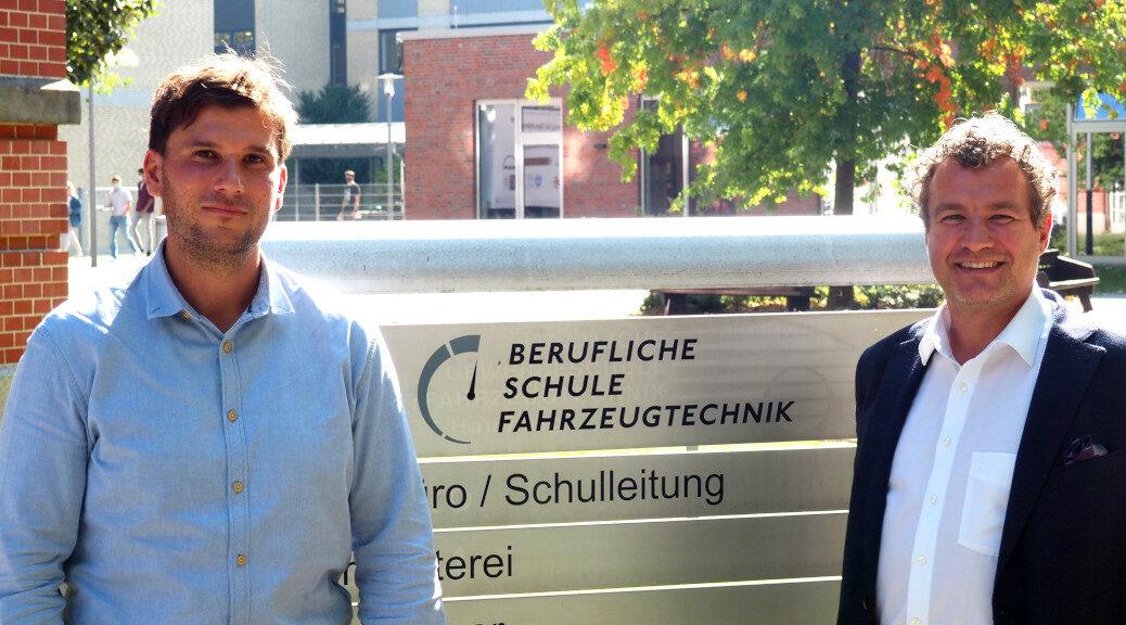 Herr Garbelmann und Herr Wranik vor dem Schullogo